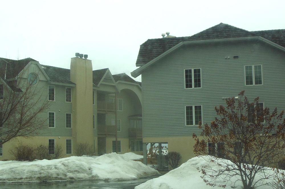 Exterior of gray, three story condo building during an overcast winter day. There are snowbanks seen on the ground.
