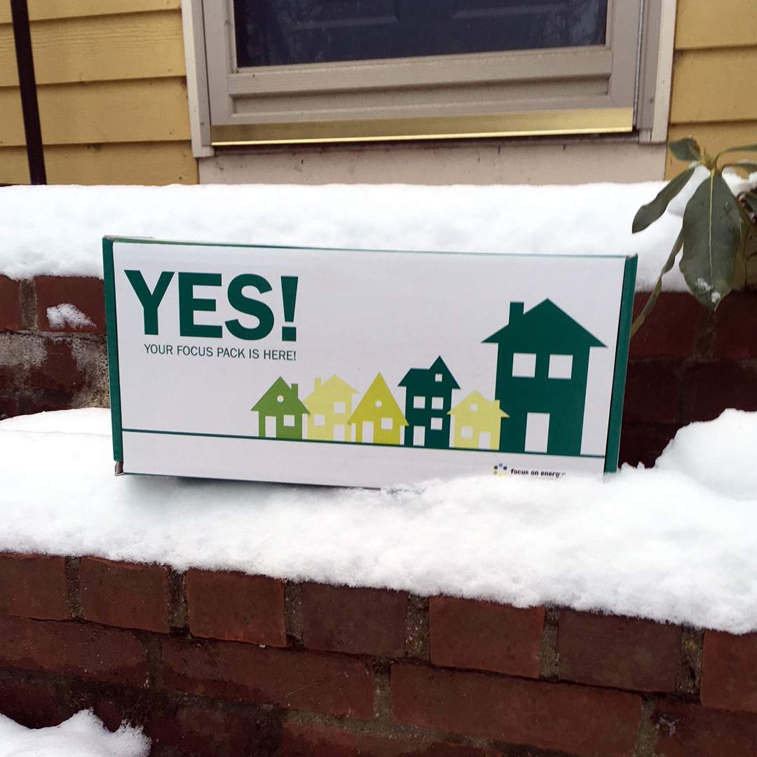 "A white box with the word ""YES!"" in green capital letters is laid on a snowy step on a brick staircase in front of a door. There are graphic images of houses on the box in yellow and green colors."