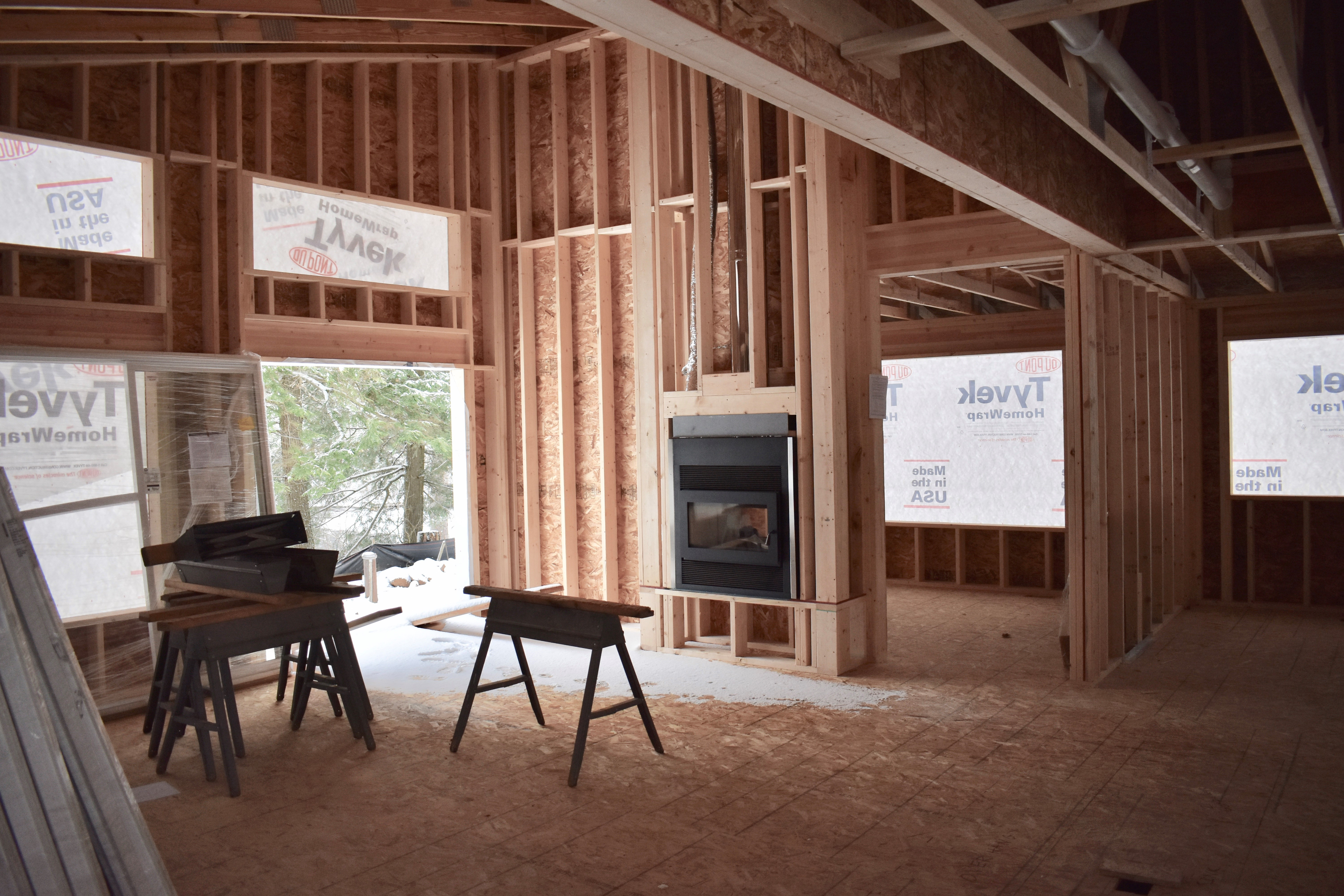 Interior of a home currently under construction - exposed beams, unfinished walls, and unfinished flooring can be seen. There is a fireplace installed in the wall.